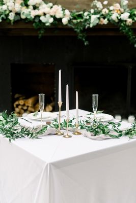 square reception table with three tapered candles of varying heights and greenery garland