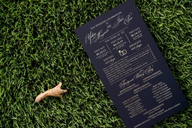 Wedding ceremony program card with story of couple and list of parents and honor attendants black