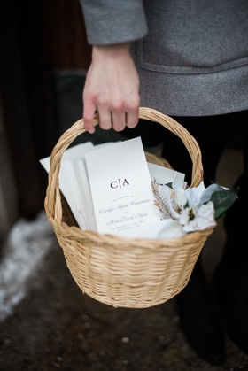 Ceremony programs with monogram in wicker basket white christmas flower on side held by attendant