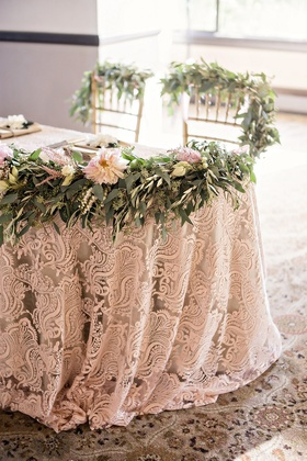 sweetheart table, patterned linens, floral garland in front, greenery of backs of chiavari chairs