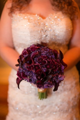 Bride holding wedding bouquet with purple flowers and calla lily blooms