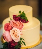 Two layer buttercream toned wedding cake with pink and red roses