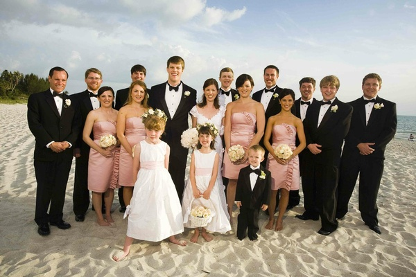 Flower girls and ring bearers with pink bridesmaids and tuxedo groomsmen