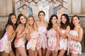 Bride with bridesmaids in matching flower print strapless romper shorts in front of bridesmaid dress
