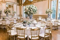 wedding reception gold ballroom blue white vases greenery white flowers gold chairs charger plates