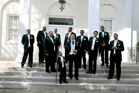 Ring bearer, groom, and groomsmen in front of church