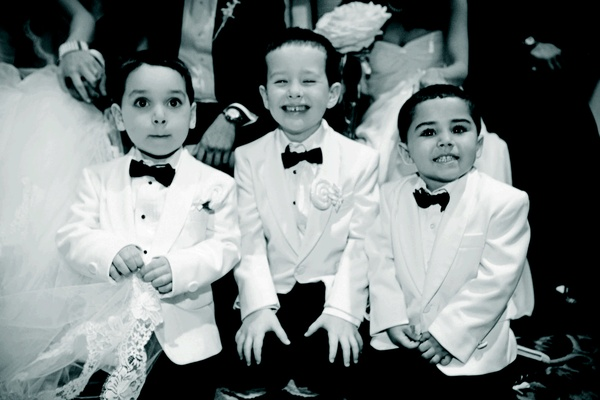 Black and white photo of three boys wearing white tuxedo jackets and bow ties at wedding