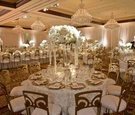 White rosette tablecloths and gold chairs