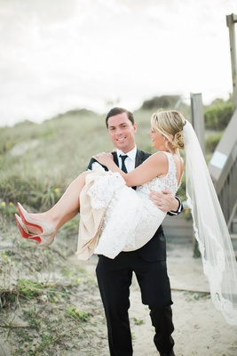 bride in alon livne lace dress carried by groom in hugo boss suit
