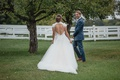 bride in keyhole back wedding dress berta with monique lhuillier overskirt blue suit for groom