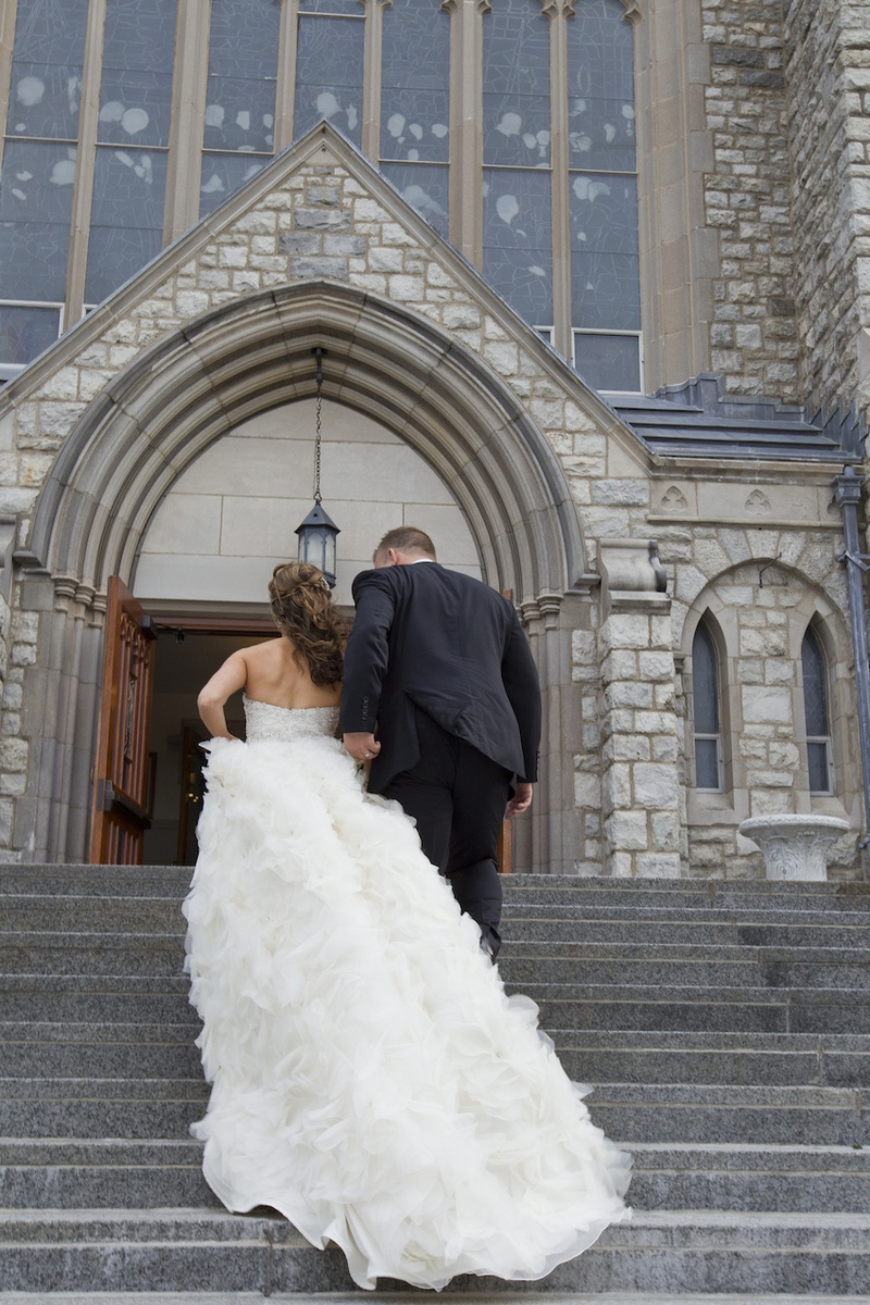 Bride in a strapless Lazaro dress with ruffly cathedral train, groom in black tuxedo at St. Teresa