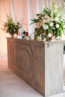 DeMarco Murray wedding bar at cocktail hour with flower arrangement and wood bar