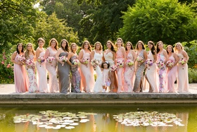 Garden wedding with fifteen bridesmaids in different dresses