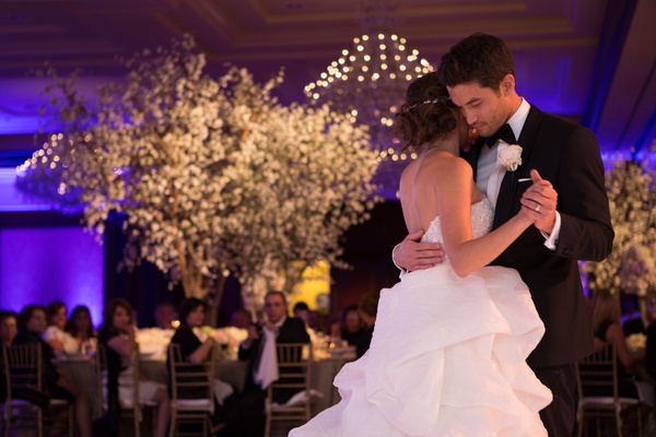 Bride in a strapless Monique Lhuillier dress with pickup skirt dances with groom in black tuxedo