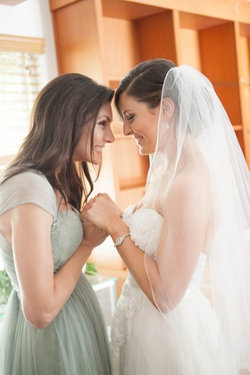 bride with her sister, maid of honor in Jenny Yoo bridesmaid dress before the wedding