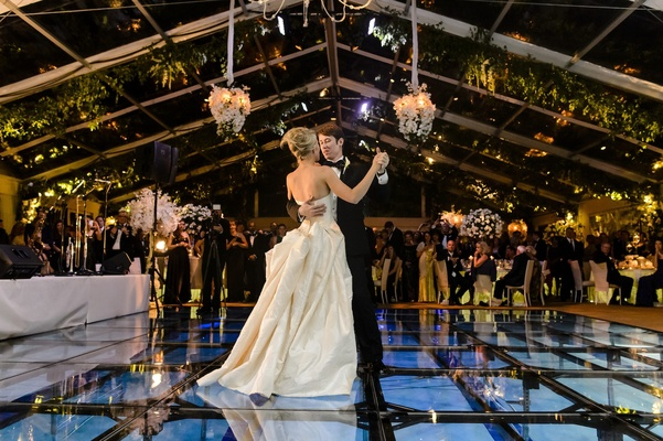 Bride and groom dance on glass-covered pool