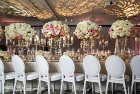 patterned uplighting, ivory and blush centerpieces, white round-backed chairs