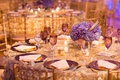 wedding reception table with purple hydrangea centerpieces and plum dinnerwear