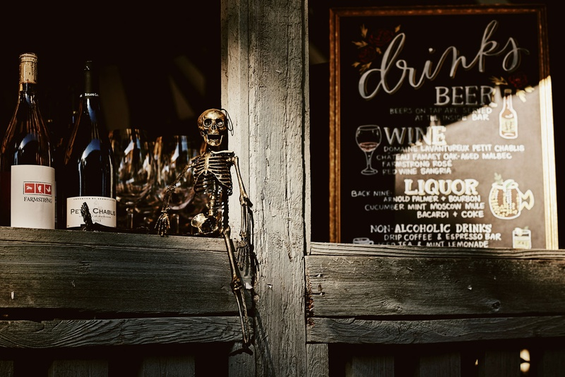 halloween theme wedding reception chalkboard drink menu skeleton on bar ledge wood