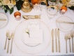 place setting white linens and plates gold detailing gold utensils glasses candles low florals