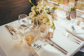 wedding reception on train car, table with small floral arrangement and detailed gold votive