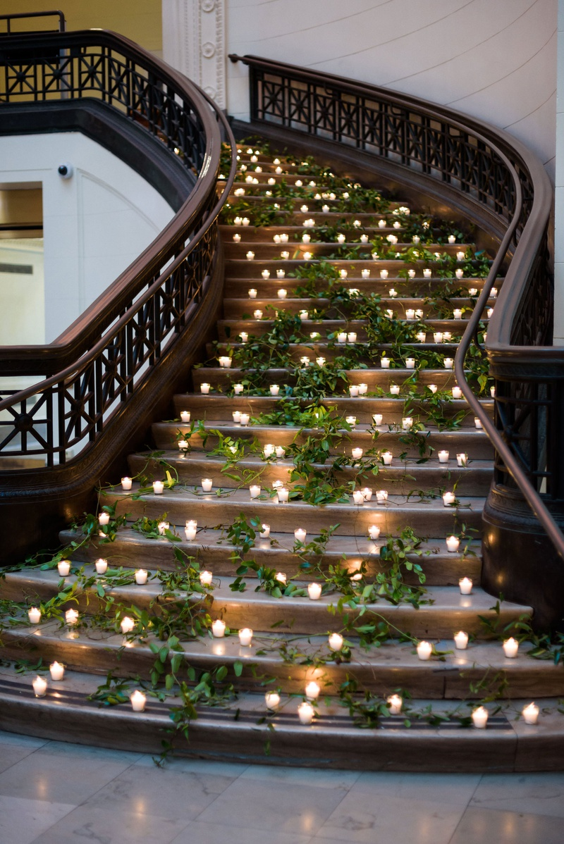 museum wedding reception decor stairss decorated with fresh greenery and candle votives