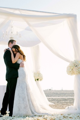 Bride in a strapless Alencon lace dress hugs groom in black tuxedo under white beach ceremony canopy