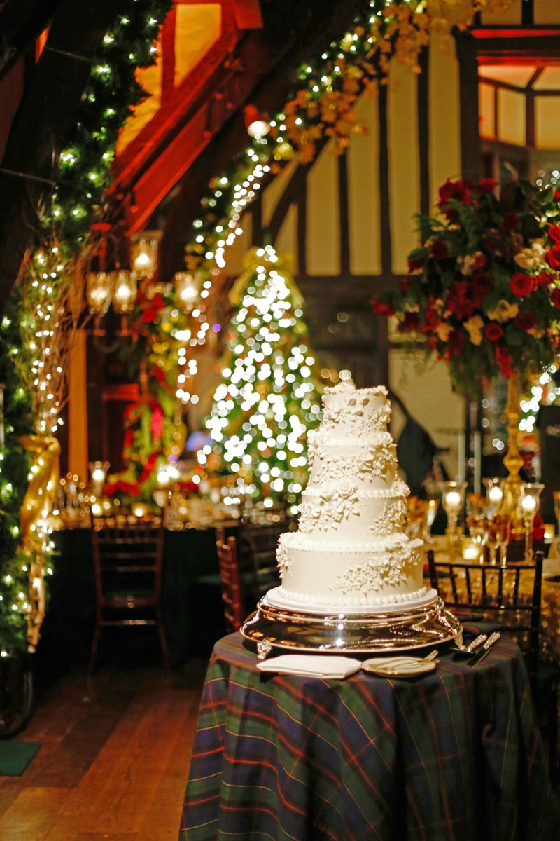 Four layer white wedding cake on plaid cake table in reception room filled with Christmas decoration