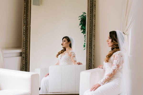 bride in lace long sleeve pronovias dress, bride reflected in mirror
