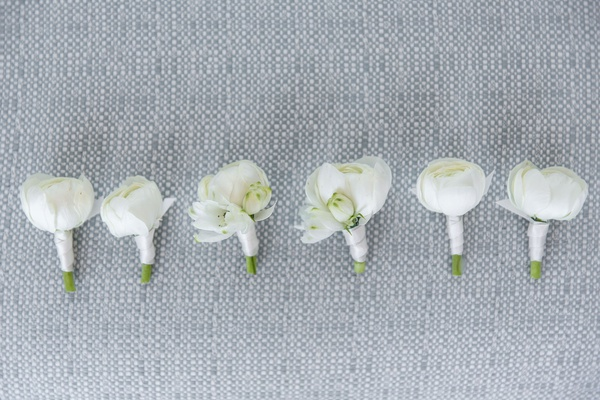 white floral boutonniere ranunculus flowers wrapped with white ribbon for groom and groomsmen