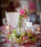 Wedding reception table with white lantern surrounded by white and green hydrangeas, pink white rose