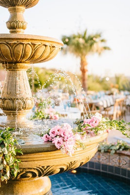 wedding reception outdoor courtyard reception palm tree stone fountain with pink flowers greenery