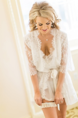 Bride slips on lace garter while wearing sheer lace robe before wedding ceremony blonde