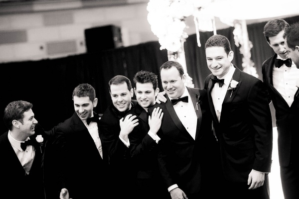 Black and white photo of groomsmen smiling in tuxedos and bow ties