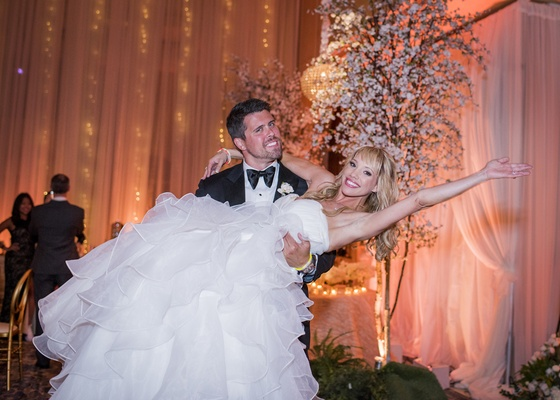 groom in tuxedo lifting up bride in wedding dress ball gown with full layered skirt