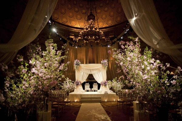 Indian Hindu wedding ceremony with large arrangements of greenery and light purple flowers