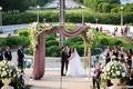 bride and groom under chuppah mauve drapery greenery birch post jewish traditions secular ceremony