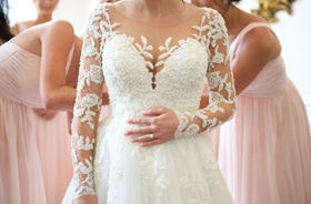 Long sleeve bridal gown with pearl applique embellishments on bodice and illusion sleeves