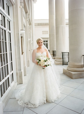 Bride in strapless oscar de la renta a line wedding dress ball gown graphic lace holding bouquet