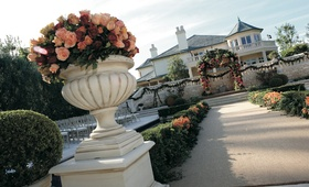 An urn full of pink, peach, and red roses decorates the start of a wedding aisle