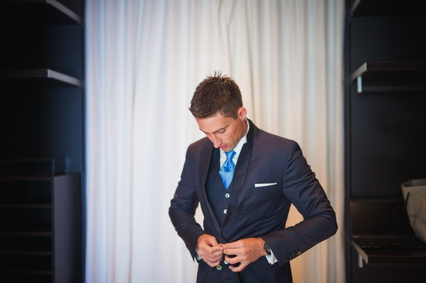 Groom's navy blue suit with blue tie.