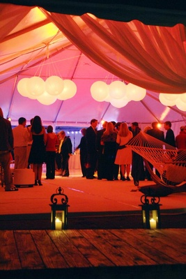 Beach wedding tent reception with paper lanterns