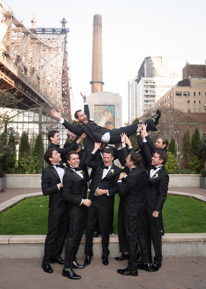 groomsmen sporting black tuxedos playfully lift the groom above their heads in NYC