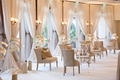 reception lounge area with neutral color palette, beige lounge furniture, white drapery ivory flower