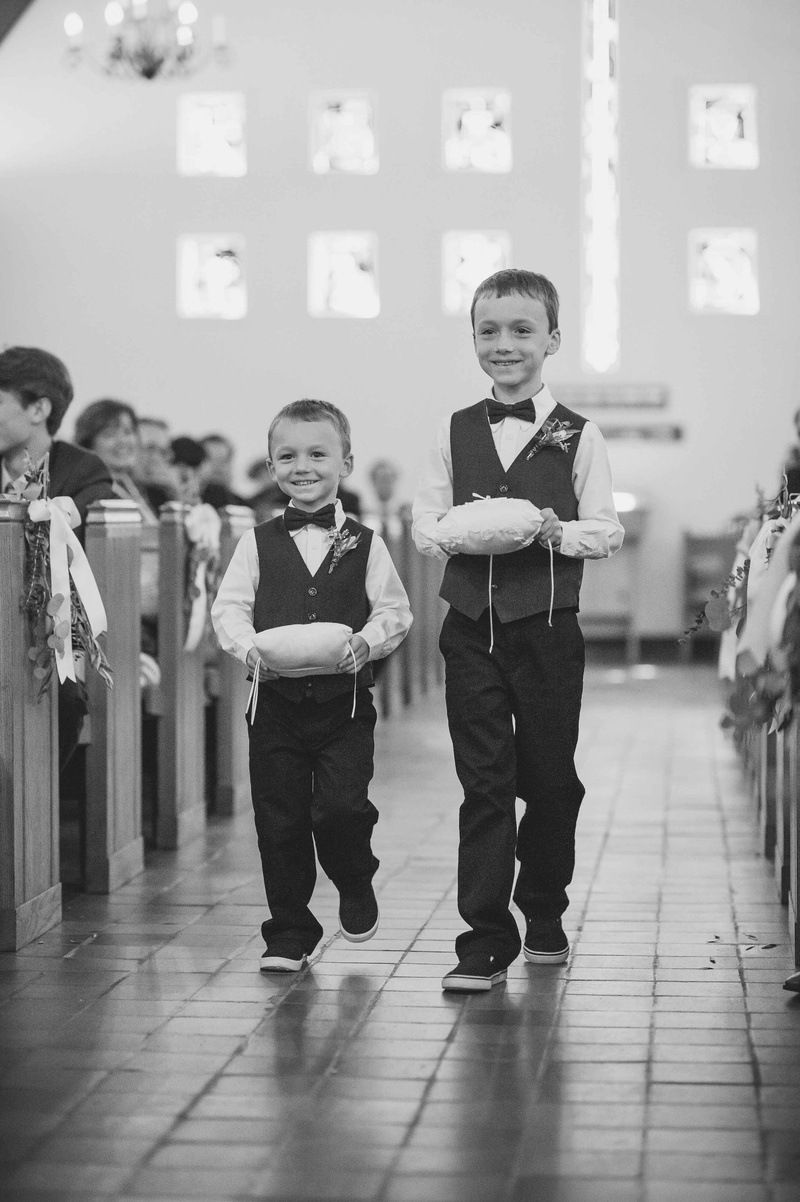 black and white photo of two rings bearers walking down aisle pillows church maine wedding smiling