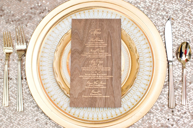 gold plateware wood menu charger plates silver sequin tablecloth calligraphy wedding reception
