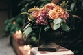 Autumn style centerpiece with burgundy and orange flowers and