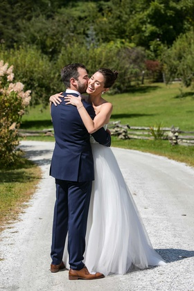 bride in strapless a line wedding dress hair up high bun groom in navy blue suit brown dress shoes