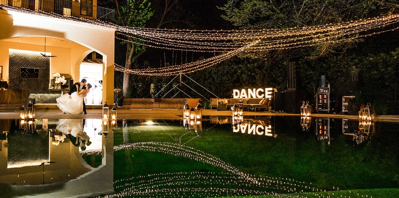 Bride and groom dancing at backyard reception