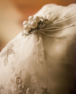White ring pillow with pearl brooch and tulle